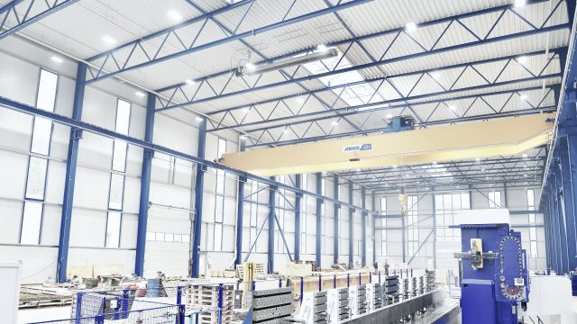 Ein Dunkelstrahler in einer großen Produktionshalle mit blauen Stahlträgern.