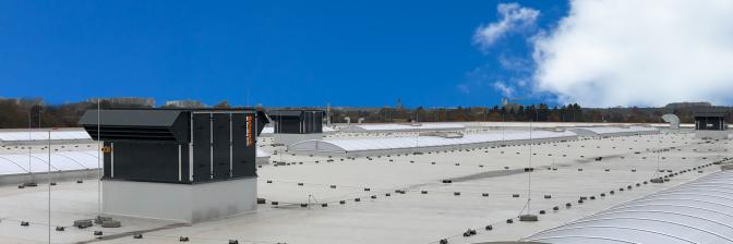 Przekrój dużego pomieszczenia z kilkoma centralami wentylacyjnymi Schwank na dachu.